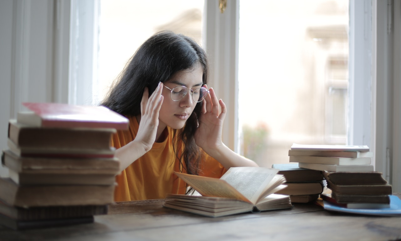 Student concentrating while sitting at a desk with stacks of books