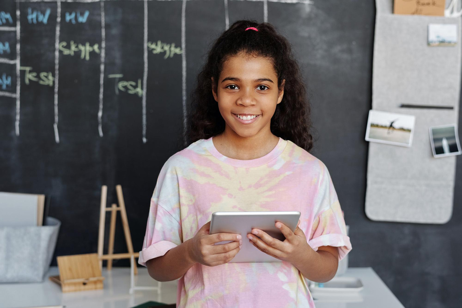 Student holding a tablet and smiling in a classroom