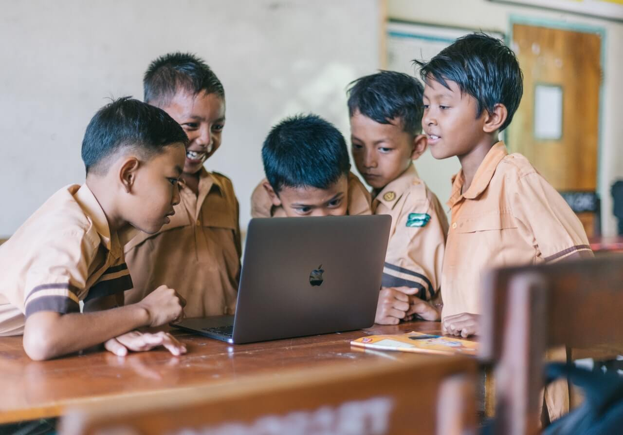 Young students gathered around a laptop in the classroom