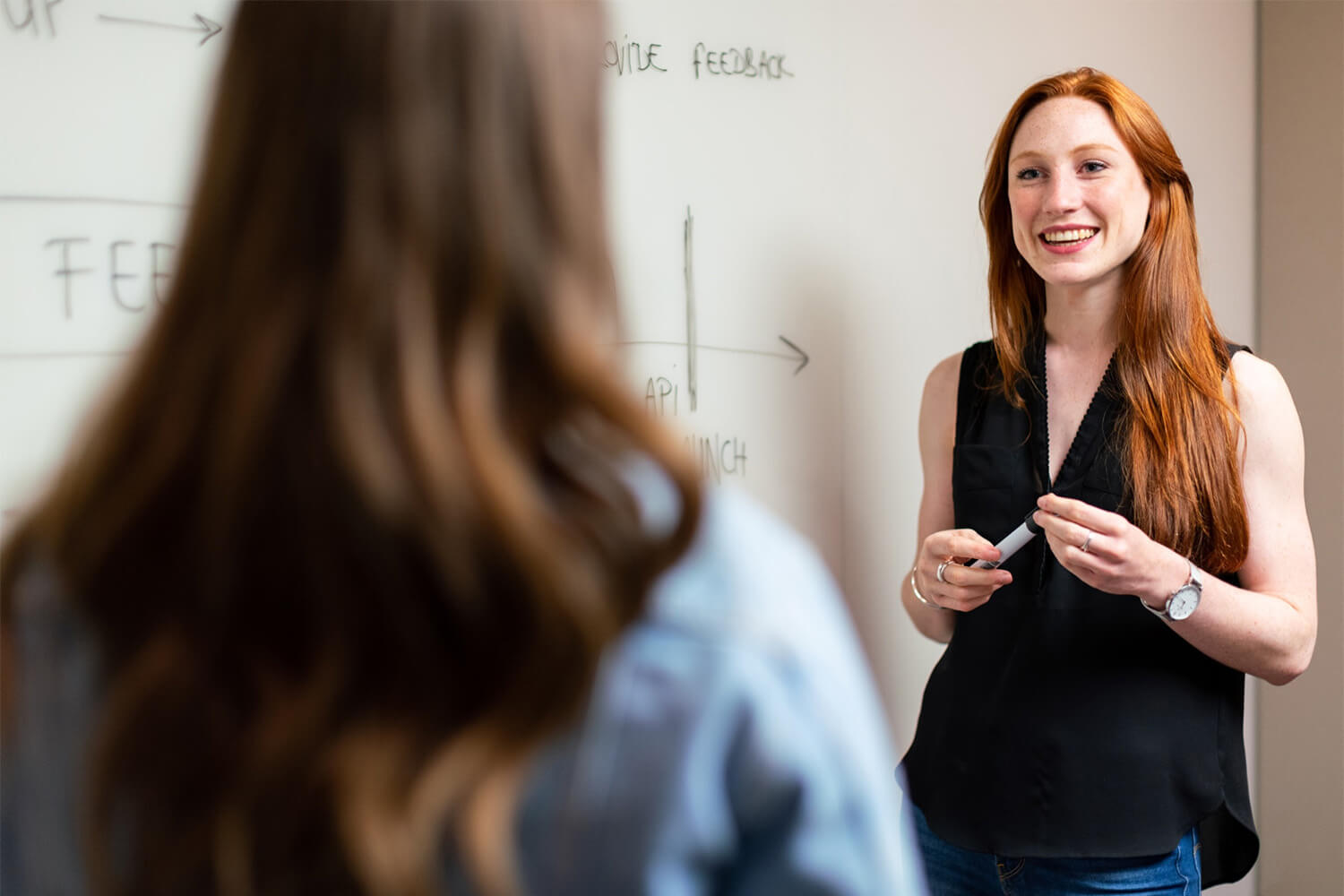 Teacher in front of a whiteboard talking to a student
