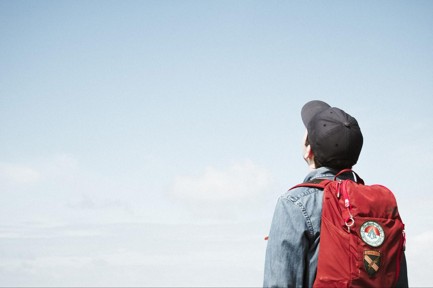 Student with a backpack looking into the sky