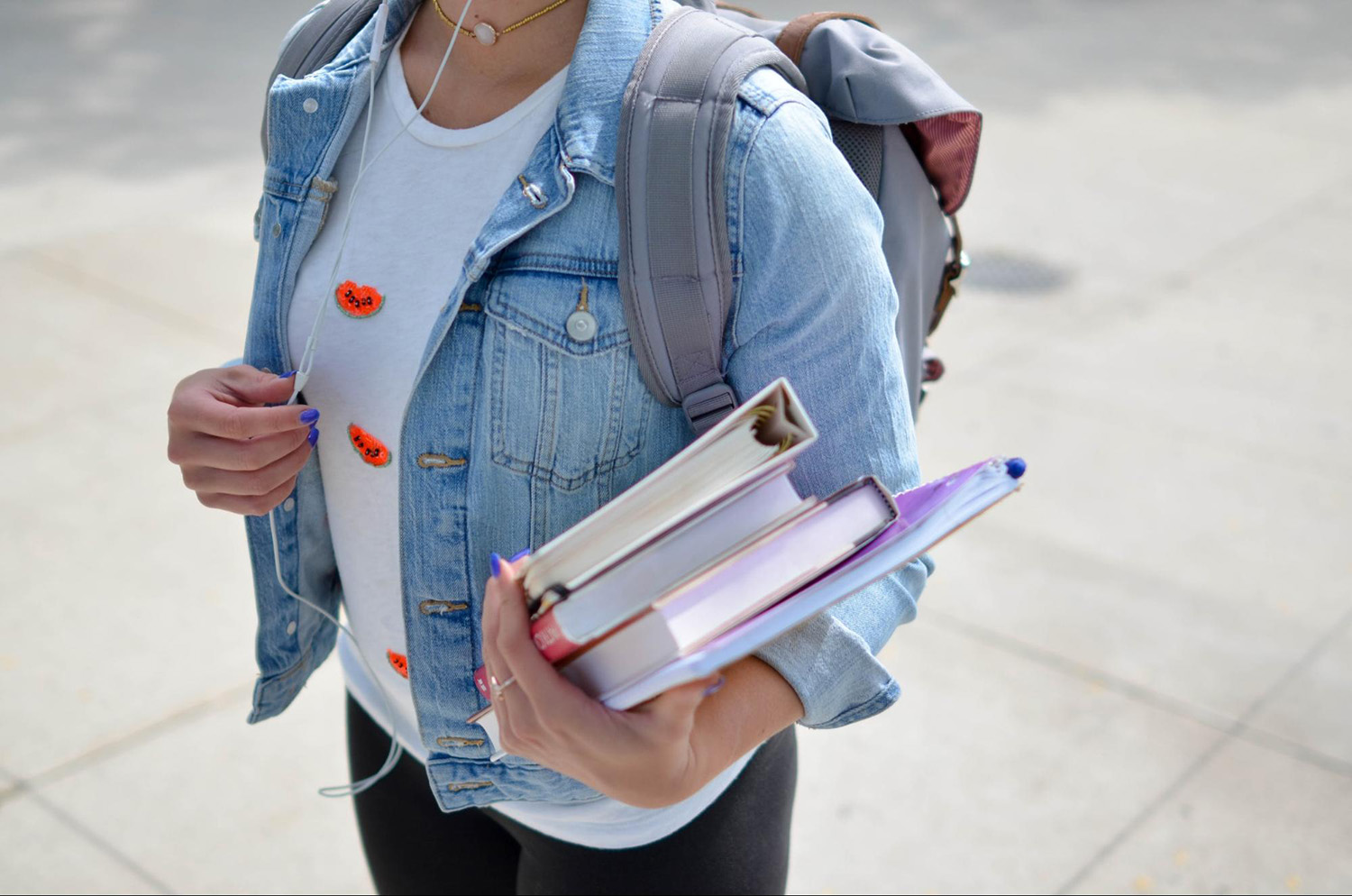 Student standing outdoors holding a backpack and textbooks