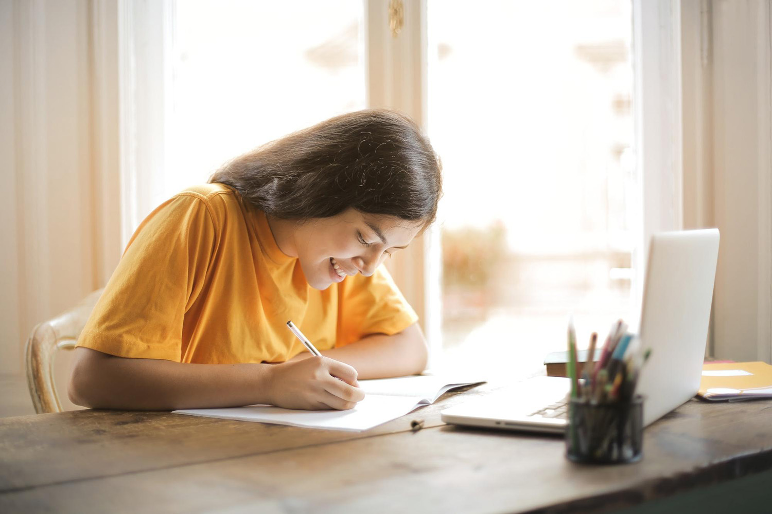 Student writing at a desk